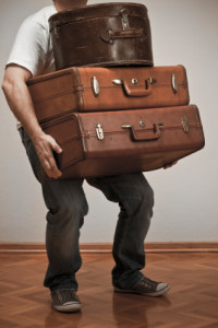 man_with_heavy_load_of_old_suitcases